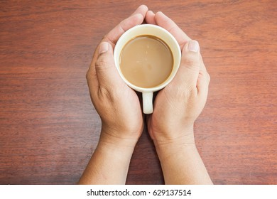 hand hold a cup of coffee on wood table