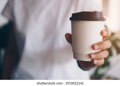 Hand hold a cup of coffee with sunlight flare beautiful copy space background. Wake up caffeine intake in morning time. - Shutterstock ID 1915012141