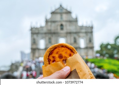 A hand hold An egg tart which is famous traditional Portuguese desserts in Macau. There is a blurred ruin of st.Pauls in background. It is a famous world heritage landmark in Macau