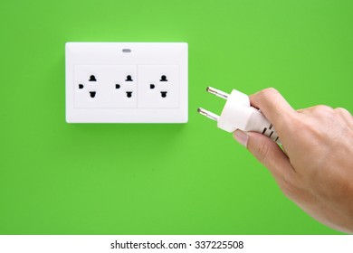 Hand hold electric power plug and inserting into power wall socket