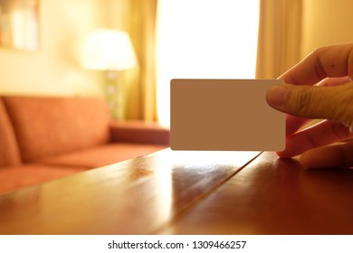 Hand hold an empty white card in a hotel room