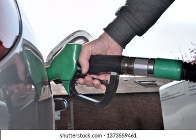 Hand hold Fuel nozzle to add fuel in car.