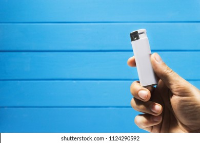 Hand hold Gasoline lighter, white plastic lighter on a blue wooden background
