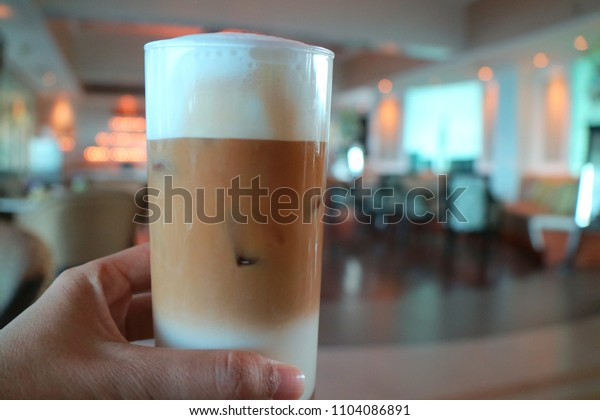 A hand hold a glass of ice coffee with blurred of interior of coffee shop background. Food and drink concept.