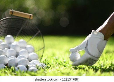Hand hold golf ball with tee on green grass for practice