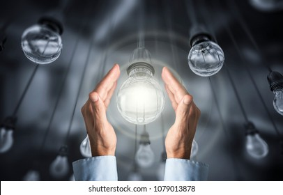 Hand hold Illuminated light bulb standing Out in Crowd,,3d render