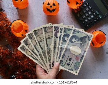 Hand hold Japanese money with pumpkin bucket, calculator and decorations ribbons on marble pattern table
