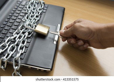 hand hold key to open padlock with chain lock on computer - computer security concept - selective focus