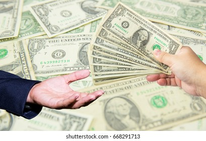 hand hold many dollar banknotes and another one act receive that money with dollar background. corruption concept.US Dollor Currency in hand.