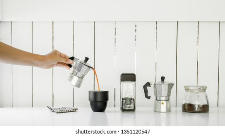 Hand hold Mokapot coffee pouring in cup with Roasted coffee beans on table ,Home interior or office white wood background