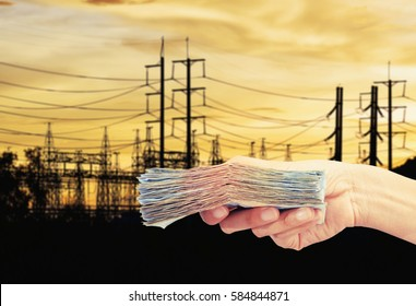 hand hold money with electric tower ,save power cost