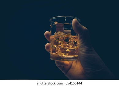 Hand hold mug of scotch whisky.