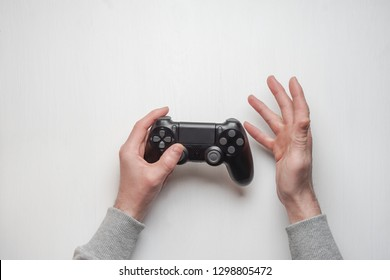 Hand hold new joystick isolated. Gamer play game with gamepad controller. Gaming man holding simulator joypad. Person with keypad joystic in arms. not understanding the situation Gaming concept.