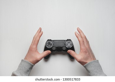 Hand hold new joystick isolated. Gamer play game with gamepad controller. Gaming man holding simulator joypad. Person with keypad joystic in arms. Sleeve hands hold toy equipment. Gaming concept.