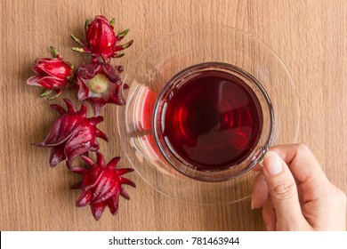 Hand hold an organic Roselle teacup for the healthy drink, Roselle healthy herbal tea rich in vitamin C and minerals.  Top view, Healthy concept
