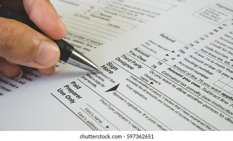 Hand hold pen on sign point on the tax forms paper in business concept.