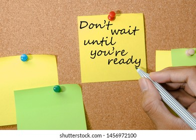"hand hold a pen wiite "" don't wait until you're ready""  phrase in memo note on cork board"