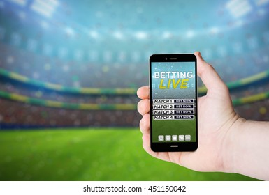 Hand hold a phone with  betting online on a screen on the background of a stadium. All screen graphics are made up.