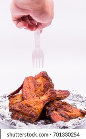 Hand hold plastic fork over leg,  wing delicious grill chicken on foil on white background