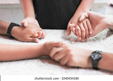 Hand hold Praying family.Mother daughter and son holding hand and pray in the table.