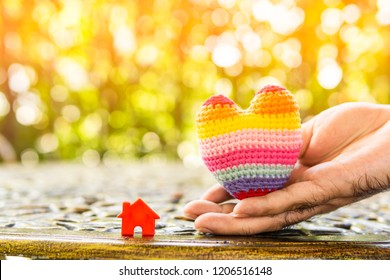 Hand are hold rainbow heart and home model.Give love to the family for happiness..Have background in garden and light of sun.