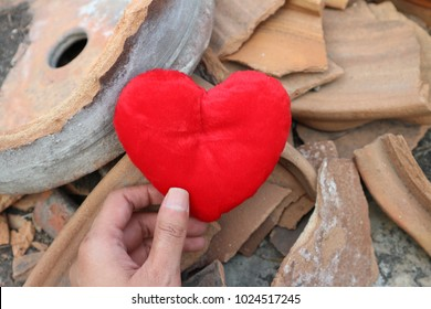Hand hold red heart in damaged pieces of broken pottery