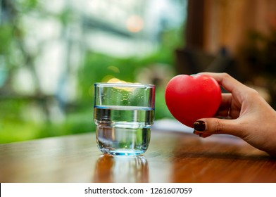 Hand Hold Red Heart with A Glass of Water. Proper hydration Good for your Brain, Mood, Body Weight and Essential for Health Heart Constantly working. The Importance of Hydration for Your Heart Concept