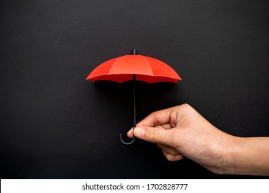Hand hold a red umbrella 3D icon isolated on black background