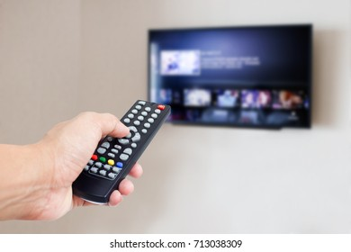 hand hold remote control with TV on wall