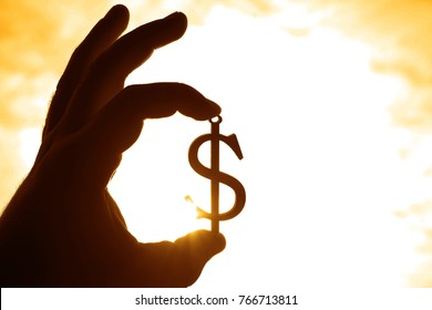 Hand hold silhouette of dollar sign , symbol of american money against sun rays and sunset sky with clouds. Dollar sign. empty copy space for inscription or other objects.