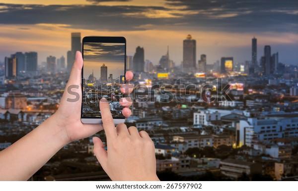 tenere la mano smart phone catturare le immagini sullo sfondo della città tramonto