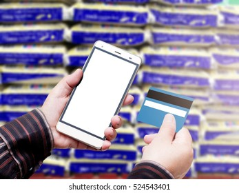 Hand Hold Smart phone with Credit Card over blurred of Shopping mall. blurry backgrounds
