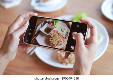 Hand hold smartphone taking photo of fried rice on dish before eating in cafe. people living lifestyle with technology and living life