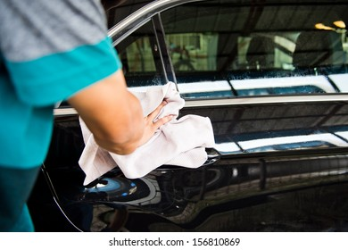 hand hold sponge over the car for washing.