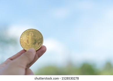 Hand hold a symbol of Bitcoins as digital money cryptocurrency with nature background with copyspace that you can put text on.