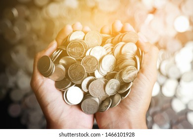 Hand hold Thai baht coins for save in finance and business background