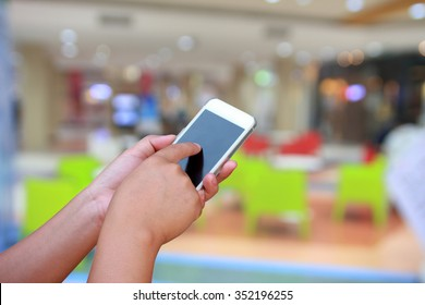hand hold and touch screen smart phone, on abstract  blurred photo coffee shop background