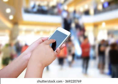 hand hold and touch screen smart phone, on blurred photo of department store shopping mall center and people background