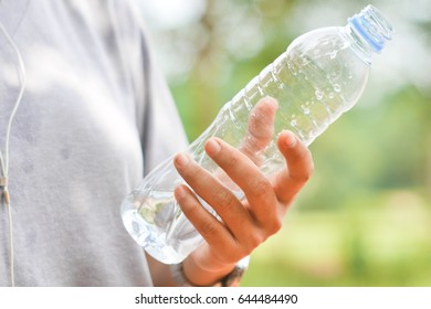 Hand hold a water bottle