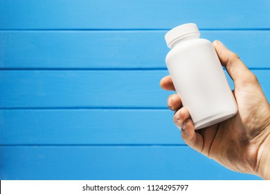 Hand hold white bottle for pills on a blue wooden background.