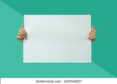 Hand hold white paper on green background
