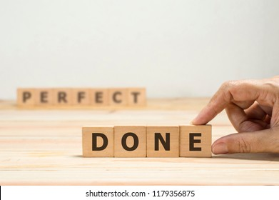 "hand hold wood block and place to complete word  ""done""  with blurred word  ""perfect""  behind , metaphor as done is better than perfect"