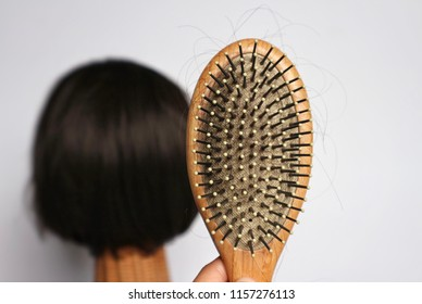 Hand hold wood comb brush with hair inside and blur model with short hair in white background