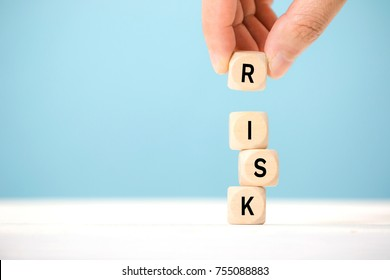 Hand hold wooden cubes with risk word. Risk management concept.