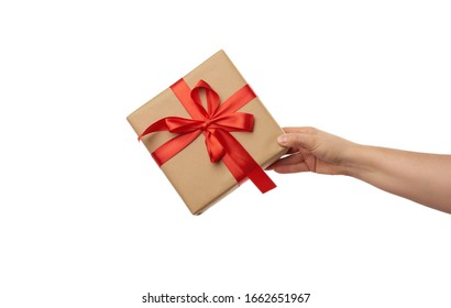 hand hold a wrapped gift in brown craft paper with tied silk red bows, subject is isolated on a white background, concept of surprise and gift for the holiday