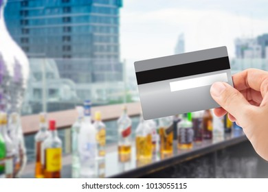 Hand holdind Credit card with blur of cocktai or alcohol on rooftop building.