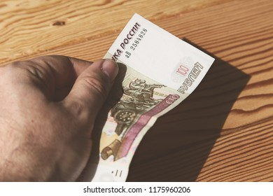 A hand holding a 100 Russian Ruble banknote. This image can be used to represent money.