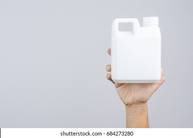 Hand holding 1000 cc, a liter plastic bottle or 0.26 gallon capacity for containing fertilizer or industrial liquid on white background