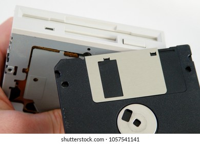 Hand holding 3 1/2 inch FDD Floppy disk drive and one floppy disk removable media