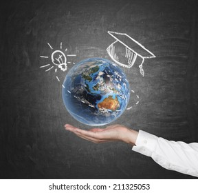 A hand holding a 3d illustration of Earth planet with sketched graduation cap and light bulb. Elements of this image furnished by NASA